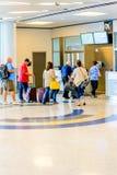Passagiere angestanden Anwäter für Einstieg an Ausgang Stockbild