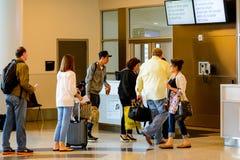 Passagiere angestanden Anwäter für Einstieg an Ausgang Stockfotos