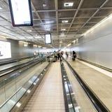 Passagiere auf einem beweglichen Gehweg im Flughafen Stockbilder