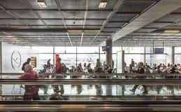 Passagiere auf einem beweglichen Gehweg und an einem Tor im Flughafen Stockfotos