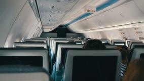 Passagiere in den bequemen Sitzen von Flugzeugen mit Karten auf Schirmen in den Stühlen stock video