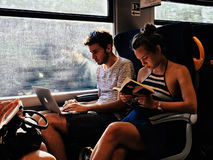 Passagiere des jungen Mannes und des Mädchens auf Zug ein Buch lesend stockfotos