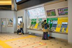 Passagiere, die Bahnfahrkarte mit Kartenmaschine in der Tokyo-Station kaufen Stockfotografie