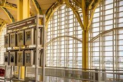 Passagiere, die durch einen hellen Flughafen gehen Stockbild