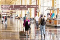 Passagiere, die durch einen hellen Flughafen gehen Lizenzfreie Stockfotos