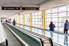 Passagiere, die durch einen hellen Flughafen gehen Stockfoto