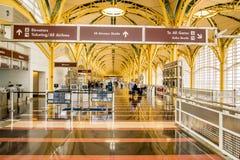 Passagiere, die durch einen hellen Flughafen gehen Stockfotografie