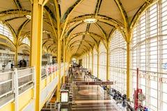 Passagiere, die durch einen hellen Flughafen gehen Stockbilder