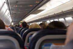 Passagiere, die im Flugzeug bereites zur Abfahrt setzen stockfotografie