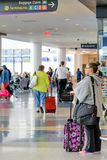 Passagiere, die mit Gepäck in einem Flughafen gehen Lizenzfreie Stockbilder