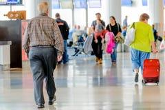 Passagiere, die mit Gepäck in einem Flughafen gehen Stockbild