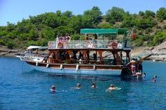 Passagiere, die um ihr Boot schwimmen Stockbild
