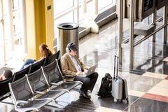 Passagiere, die vor einem hellen Innenflughafenfenster warten Stockbilder