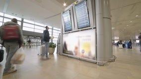 Passagiere an einem Flughafenabfertigungsgebäude, das Abfahrtstafel betrachtet stock video