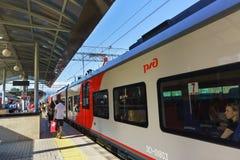 Passagiere gehen entlang die Plattform hinter den Nahverkehrszügen am Bahnhof sonnigen Tages Sochis Lizenzfreie Stockfotos