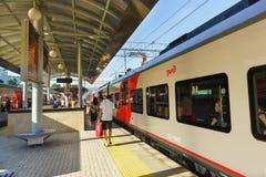 Passagiere gehen entlang die Plattform hinter den Nahverkehrszügen am Bahnhof von Sochi Lizenzfreie Stockfotografie