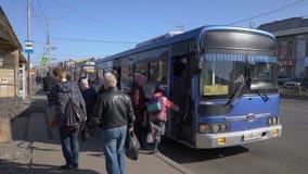 Passagiere gehen heraus und steigen in den allgemeinen Bus der blauen Stadt an der Bushaltestelle auf Stadtstraße ein stock video