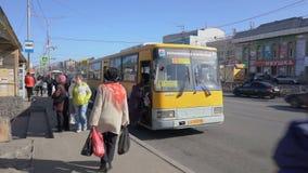 Passagiere gehen heraus und steigen in den allgemeinen Bus der gelben Stadt an der Bushaltestelle auf Stadtstraße ein stock video