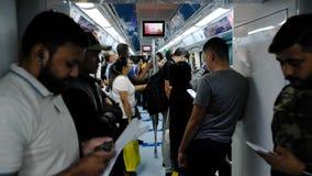 Passagiere, größtenteils Gastarbeiter, reiten die U-Bahn und betrachten ihre Telefone Dubai, im Januar 2019 stock video