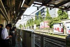 Passagiere warten auf den Zug am Bahnhof stockbild