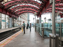 Passagiere warten auf Docklands-Kleinbahnzug bei zitronengelbem Whar Stockfotos