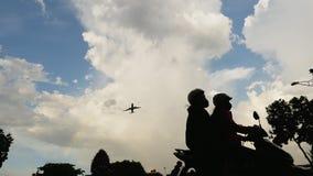 Passagierflugzeug, das bei Sonnenuntergang vor dem hintergrund sehr schöne Wolken und Straßen mit Verkehr entfernt stock video footage