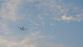 Passagierflugzeug entfernt sich gegen den blauen Himmel mit Wolken stock footage