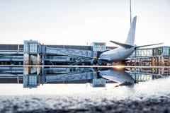Passagierflugzeug geparkt zu einer Luftbrücke mit Reflexion in einer Pfütze stockbild