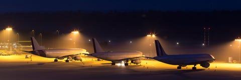 Passagierflugzeuge, die auf ein aiport nachts warten Stockbild