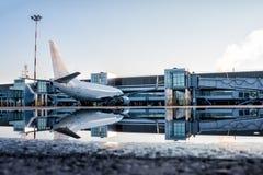 Passagierflugzeuge geparkt zu einem jetway mit Reflexion in einer Pfütze lizenzfreie stockbilder