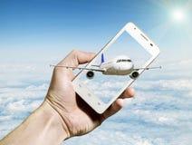 Passagierflugzeugfliegen aus Smartphoneschirm gegen bewölkten Landscap heraus Lizenzfreie Stockfotos