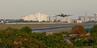 Passagierflugzeugstart-Flugplatzstreifen auf dem Hintergrund der Stadt Lizenzfreies Stockfoto