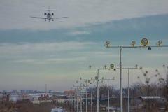 Passagierpassagierflugzeugdurchläufe über den Landescheinwerfern und Landung am Flughafen stockfotos