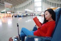 Passagierreisendfrau im Bahnhof und in gelesenem Buch lizenzfreie stockfotos