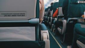 Passagiers binnen de cabine van de zitting van passagiersvliegtuigen op de stoelen tijdens de vlucht stock footage