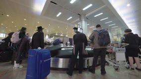 Passagiers die bagage van een transportband verzamelen bij de luchthaven stock videobeelden