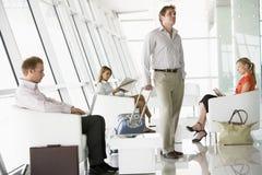 Passagiers die in de zitkamer van het luchthavenvertrek wachten Stock Foto's