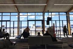 Passagiers die in de zitkamer van het luchthavenvertrek wachten Paar, het controleren royalty-vrije stock afbeeldingen