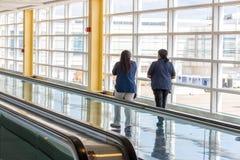 Passagiers die door een heldere luchthaven lopen Stock Afbeelding
