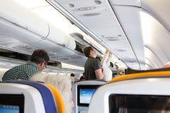 Passagiers die hun bagage van het luchtcompartiment nemen Royalty-vrije Stock Foto