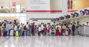Passagiers die omhoog in incheckbalie in Hong Kong International Airport een rij vormen Stock Foto's