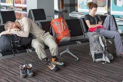 Passagiers die op de luchtvlucht wachten bij luchthaven Stock Fotografie