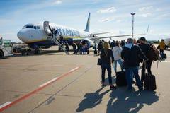 Passagiers die op de vliegtuigen van lage kostenluchtvaartmaatschappij Ryanair inschepen Stock Foto