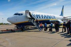 Passagiers die op de vliegtuigen van lage kostenluchtvaartmaatschappij Ryanair inschepen Stock Afbeelding