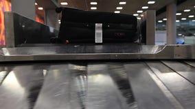 Passagiers die op hun bagage in luchthaven wachten stock videobeelden