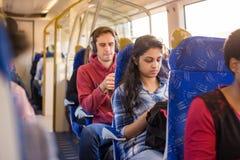 Passagiers die op trein hun mobiele telefoons bekijken stock afbeeldingen