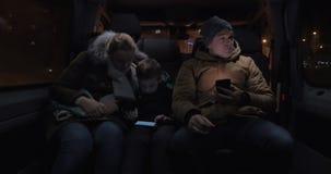Passagiers in minibus die de tijd met cellphones overgaan stock video