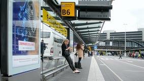 Passagiers op bushalte in de Luchthaven Schiphol van Amsterdam, stock footage