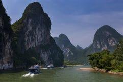 Passagiersboten met toeristen in Li River met de lange kalksteenpieken op de achtergrond dichtbij Yangshuo in China Stock Foto