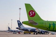 Passagiersstralen van S7 Airlines en Aurora Airlines op vliegveld Vliegtuigfuselages Luchtvaart en vervoer royalty-vrije stock fotografie